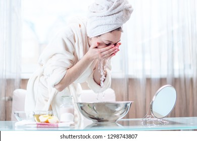 Beautiful young woman with a towel on her head washing her face with water in the morning. Concept of hygiene and care for the skin at home