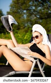 Schöne junge Frau mit Handtuch auf ihrem Haar liest Zeitung nahe dem Hotelpool