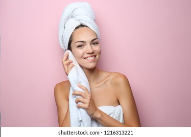 Beautiful young woman with towel wiping skin after shower on color background