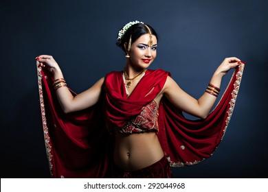 Beautiful young woman in traditional indian clothing dancing