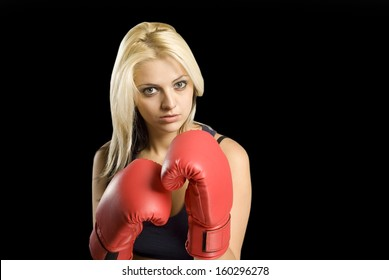 Beautiful young woman training with boxing gloves on blackboard background