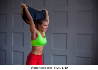 beautiful young woman is training with a sandbag in the gym.