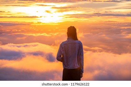 Beautiful young woman traveler enjoying sunrise and thinking about inspiration.Female tourist relaxing and admiring breathtaking view of green mountains covered fog