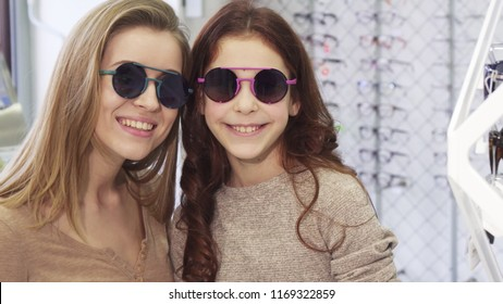 Beautiful young woman trying on sunglasses with her cute little sister