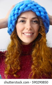 Beautiful young woman trying on knitted cap in modern shop