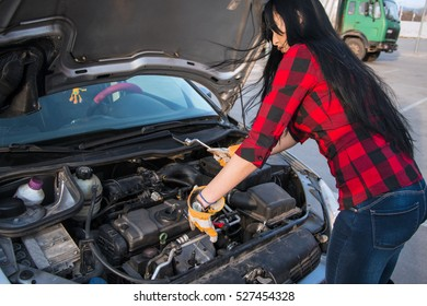 A beautiful young woman trying to repair the car