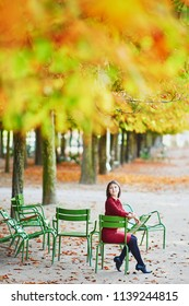 Beautiful young woman in Tuileries garden of Paris on a bright fall day. Tourism and vacation in France at autumn season