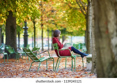 Beautiful young woman in Tuileries garden of Paris on a bright fall day, taking selfie with her mobile phone. Tourism and vacation in France at autumn season