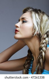 beautiful young woman in turquoise dress with long blond braids
