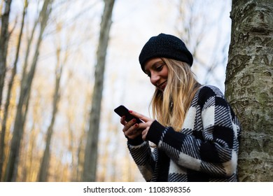 Beautiful young woman typing a text message on phone in park, smiling (selective focus)