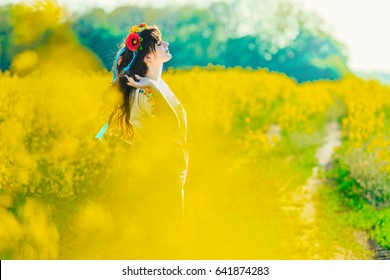 Beautiful young woman in Ukrainian embroidered standing in a field of yellow rape flowers.Attractive brunette in Ukrainian national costume on a dirt road
