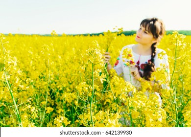 Beautiful young woman in Ukrainian embroidered standing in a field of yellow rape flowers.Attractive brunette holding a bouquet of yellow flowers
