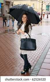 Beautiful young woman with umbrella in street