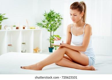 Beautiful young woman in underwear applying body lotion.