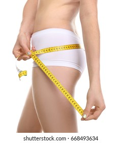 Beautiful young woman in underwear with measuring tape on white background, closeup. Diet concept