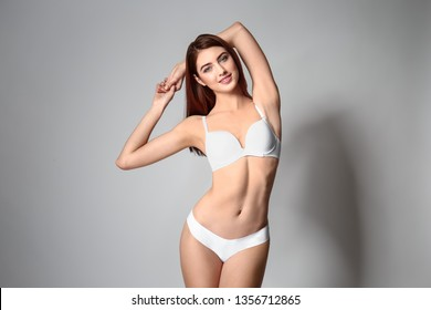 Beautiful young woman in underwear on grey background