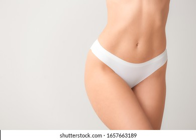 Beautiful young woman in underwear on light background. Concept of plastic surgery