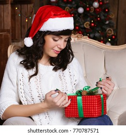 Beautiful young woman unwrapping  a Christmas present sitting in front of a decorated new year tree. Girl in Santa hat