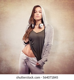Beautiful young woman in urban outfit with headphones. Studio shot