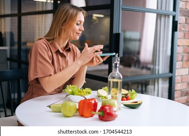 Beautiful young woman uses smartphone for taking photos of vegetables lying on kitchen table. Concept of social networks. Concept of healthy eating.