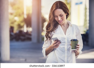 beautiful young woman is using an app in her smartphone device to send a text message in front of a sunset background