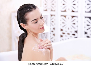 Beautiful young woman using cosmetics while taking bath at home