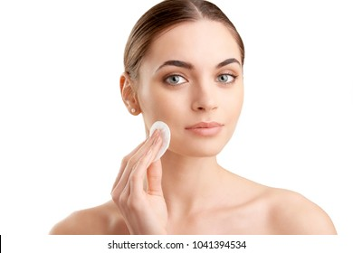 Beautiful young woman using cotton pad while cleansing her face. Isolated at white background. Daily routine.