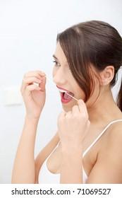 Beautiful young woman using dental floss at bathroom