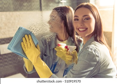 Beautiful young woman is using a detergent and a duster, looking at camera and smiling while cleaning a mirror in bathroom