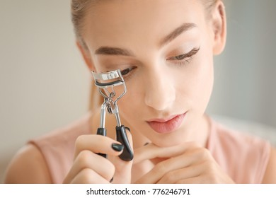 Beautiful young woman using eyelash curler, closeup