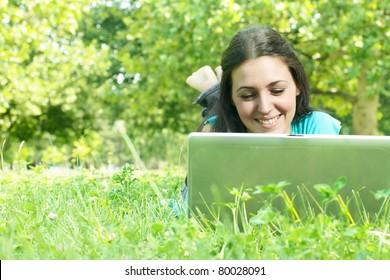 Beautiful young woman using laptop outdoors.