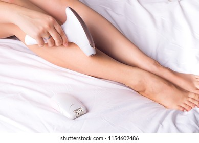 Beautiful young woman using a photoepilator for a hair and removing hair with special equipment at home