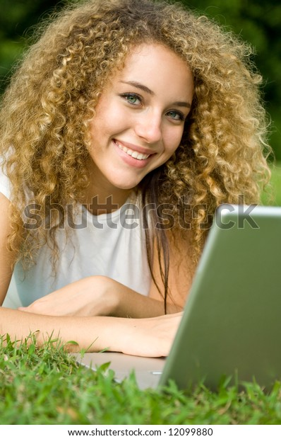 A beautiful young woman using a portable computer outside