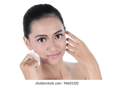 beautiful young woman using a powder on the cheeks, isolated on white background