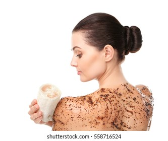 Beautiful young woman using wisp and scrub on white background