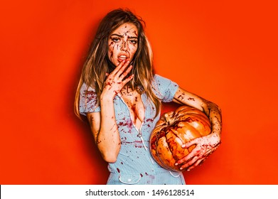 Beautiful Young woman vampire - halloween concept. Scary bloody zombie girl with pumpkin. Woman with red blood and with blond hair