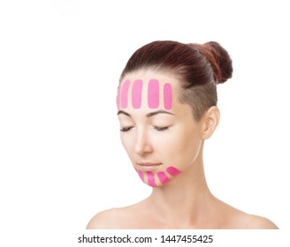 Beautiful young woman with vertical kinesio tapes on her forehead and chin for facelift, beauty procedure. Copy-space in left part of image.