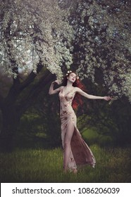 Beautiful young woman with very long red hair in a golden dress under a flowering tree , walking through the spring forest. Long red hair develops in the wind.