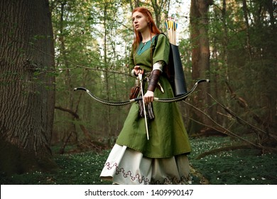 A beautiful young woman with very long red hair walks with a bow through the autumn forest. Redhead Girl hunting in wood