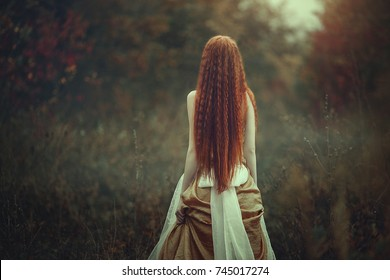 A beautiful young woman with very long red hair as a witch walks through the autumn forest. Back view.