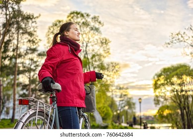 Beautiful young woman with a vintage bicycle in a park.