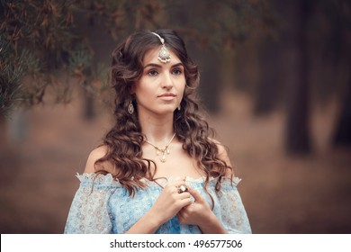 Beautiful young woman in vintage blue dress in the evening forest