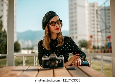 beautiful young woman in vintage dress posing for a photographer with a retro camera in her hands. without retoching
