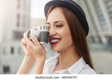 Beautiful young woman in vintage style in the hat makes the photo. Vintage style. Tourism