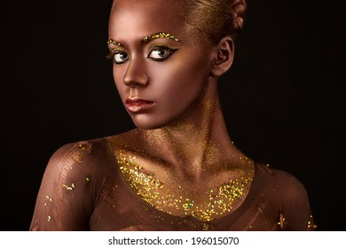 and beautiful young woman with a beautiful visage and gold sequins on the body