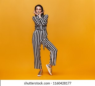 Beautiful young woman with vivid make up in studio. Portrait of fashion model in striped jumpsuit standing over orange background.