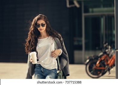 beautiful young woman waiting for some in front of the office building with cup of coffee in her hand. businesswoman is dressed very fashionably wearing sunglasses. background with a bicycle rack