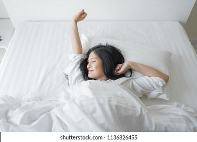 Beautiful young woman wake up and stretch oneself in the morning at bedroom.