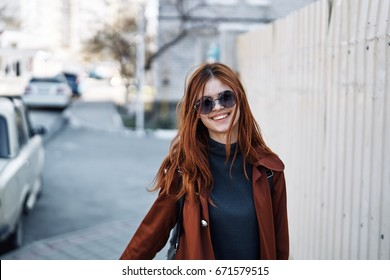 Beautiful young woman is walking along the street in sunglasses.