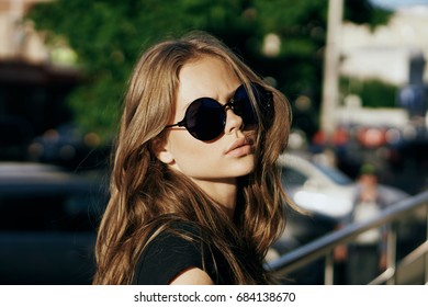 Beautiful young woman is walking along the street in the city in summer.